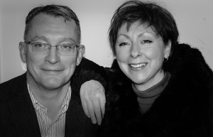 David Boyes and Phyllis Joyce, hosts of the Talk To Phil & Dave Show on Pulse 98.4 community radio. Black and white photo.